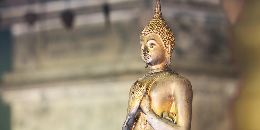 Eine goldfarbene Buddhastatue hat beide Hände auf die Brust gelegt, eine Geste der Dankbarkeit.