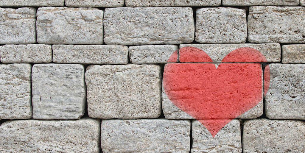 Eine Mauer aus Steinen ist zu sehen, auf die ein rotes Herz gesprüht ist. Die Mauer symbolisiert innere Mauern.