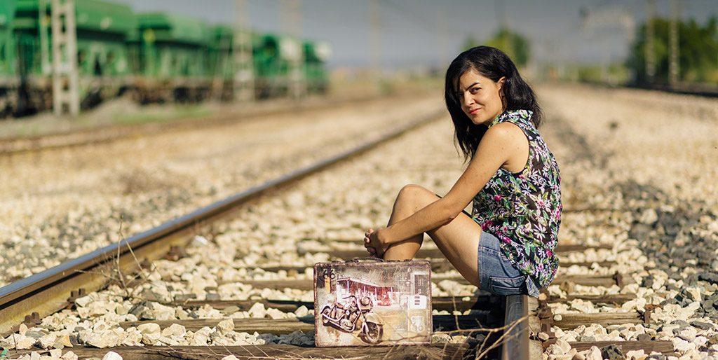 Eine Frau mit einem kleinen Koffer sitzt auf einem Gleis, sie wartet darauf, dass der richtige Moment kommt.