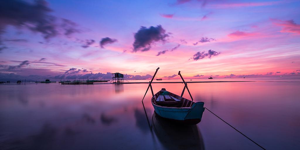 Ein Ruderboot liegt auf einem ruhigen See bei Sonnenaufgaben.