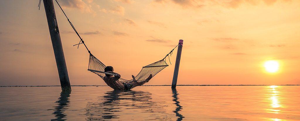Ein Mann widmet sich in einer Hängematte über dem ruhigem Meer dem Müßiggang und genießt den Sonnenuntergang.