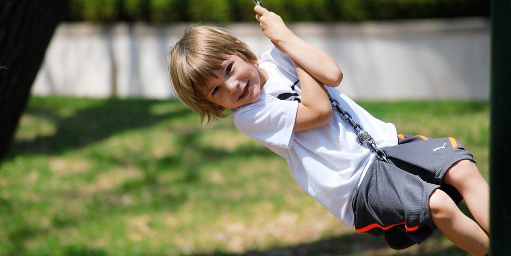 Ein kleiner Junge schwingt auf einer Schaukel so ausgelassen wie das innere Kind in uns sich zeigen will.