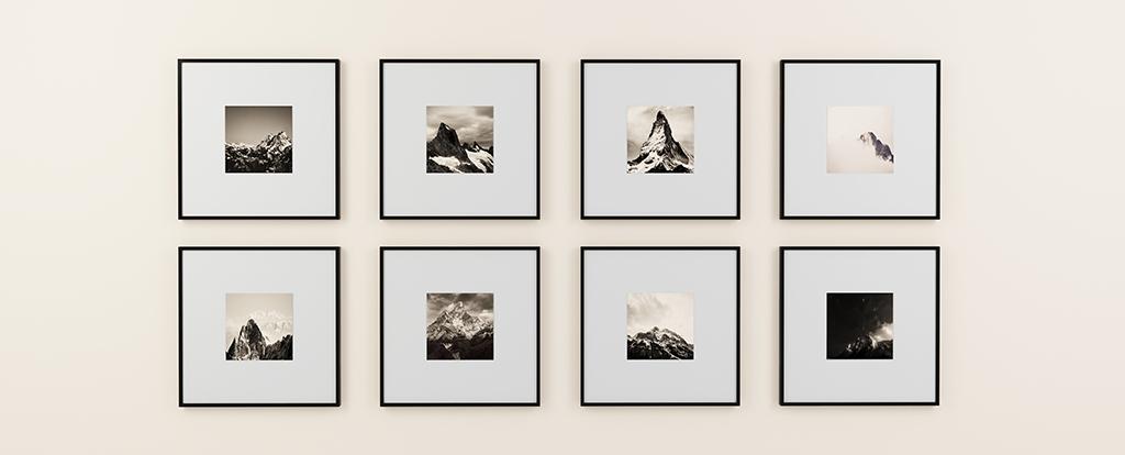 Acht schwarz-weiß Bilder hängen an einer Wand.
