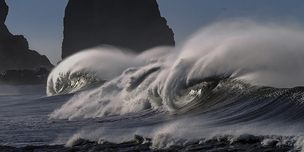 Aufgewühlte Wellen schäumen hoch auf, im Hintergrund ist ein dunkler Felsen zu sehen - ein Sinnbild für das Schwere in der Welt.