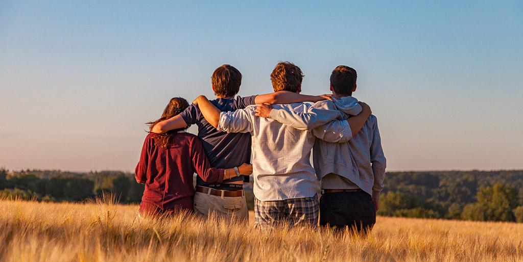 Vier junge Menschen stehen Arm in Arm in einem Feld reifer Ähren.